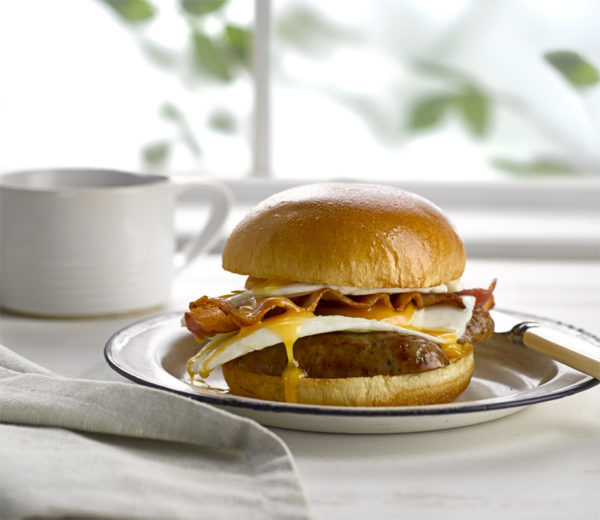 Breakfast Brioche burger with sausage bacon and egg, and a cup of coffee in the background