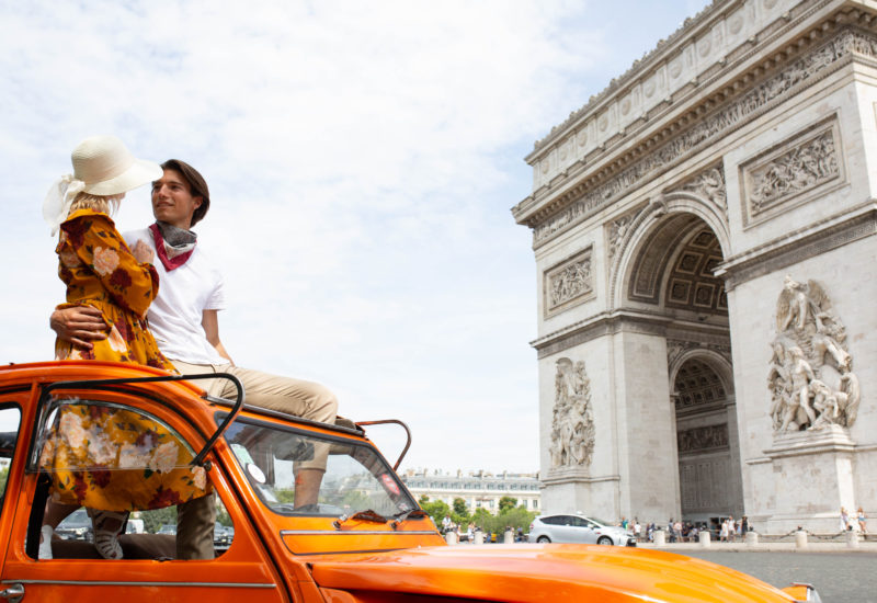 couple in orange car in front of the Arc de Triomphe
