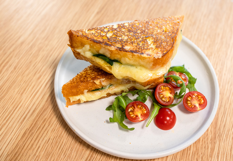 A Brioche Grilled Cheese Sandwich recipe on a white plate next to lettuce and tomatoes