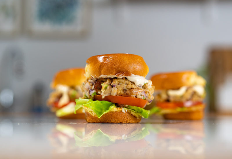 A photo of three small crab cake burgers on a table